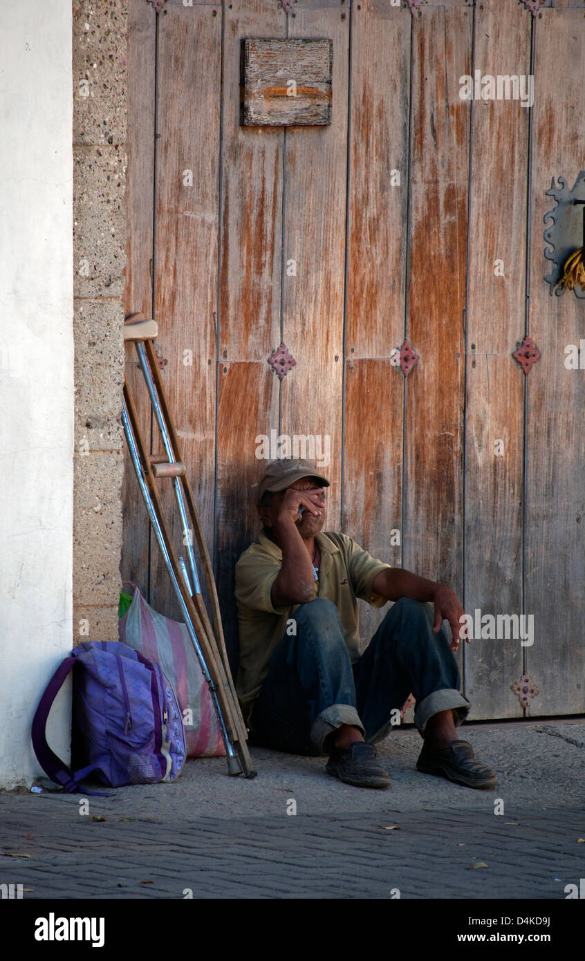 Man alone and homeless on the street in Comayagua, Honduras, with crutches and belongings in plastic bag. - Stock Image
