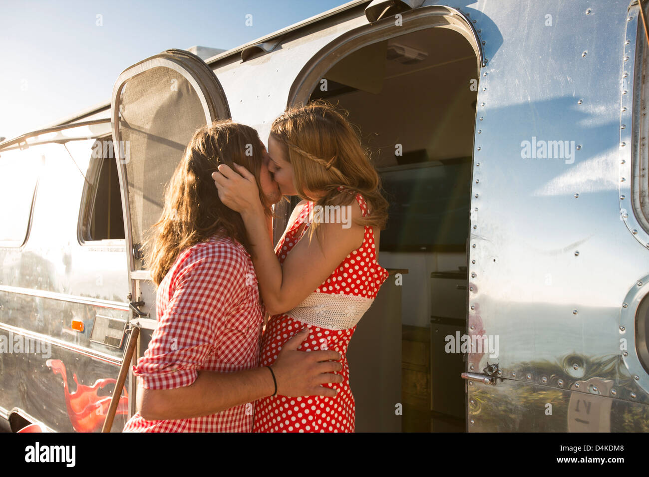 Couple kissing by trailer - Stock Image