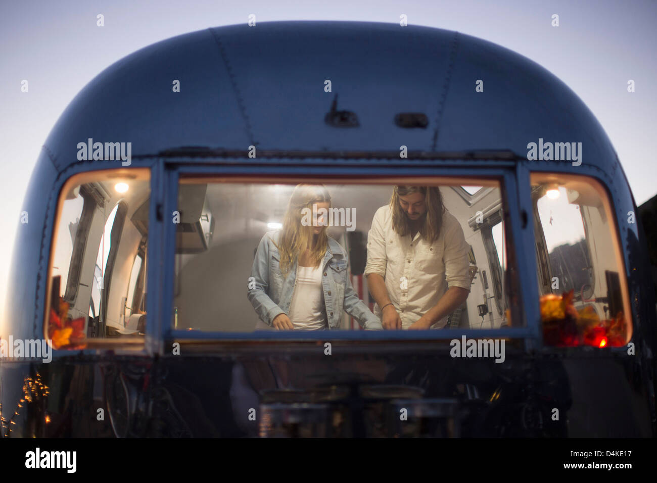 Couple cooking together in trailer - Stock Image