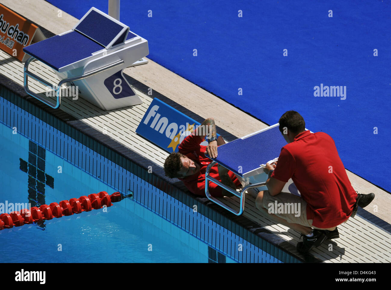 A staff member of time measurement comapny Omega adjusts starting blocks for the upcoming swimming events at the Stock Photo