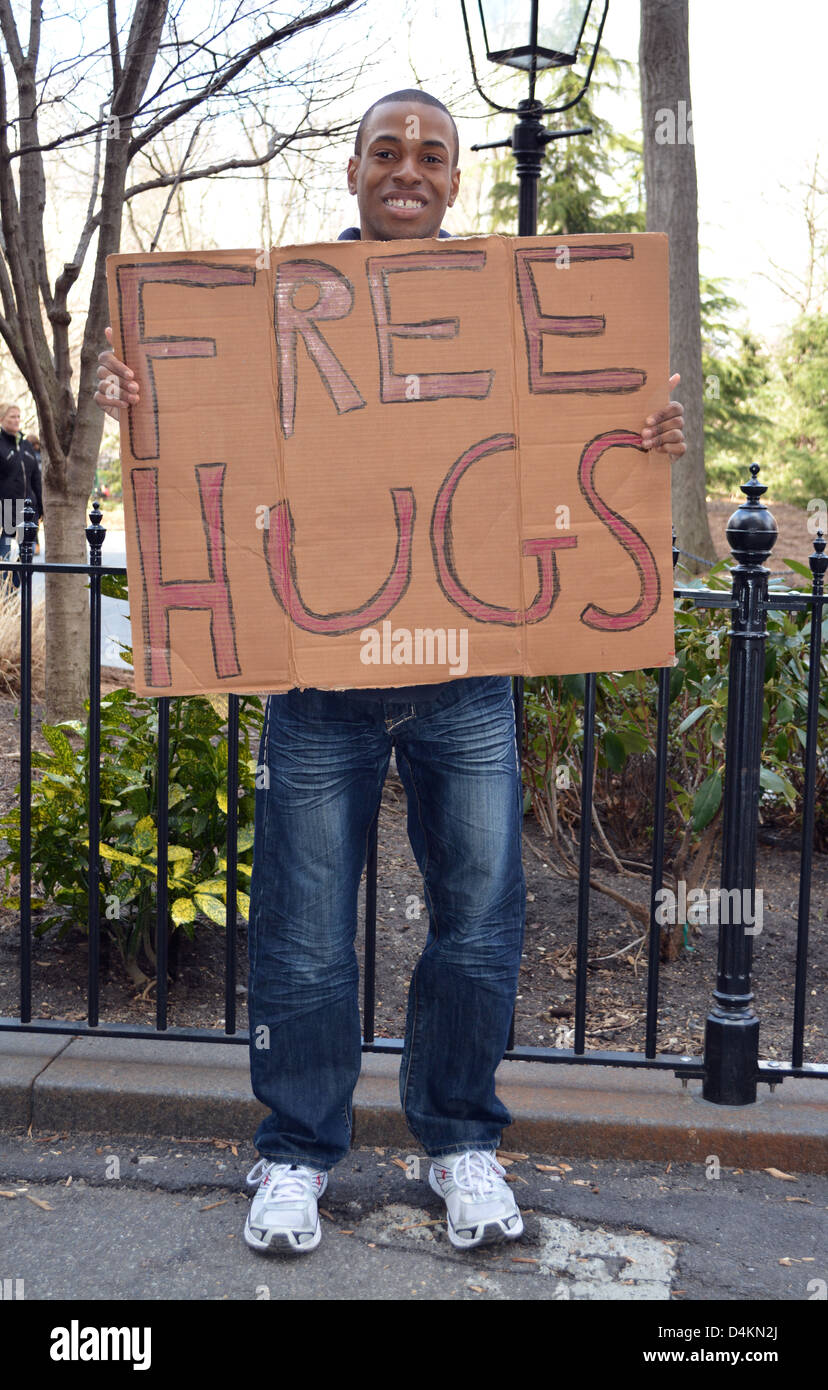 Unemployed recent college graduate tries to earn some money by offering free hugs and asking for a donation. - Stock Image