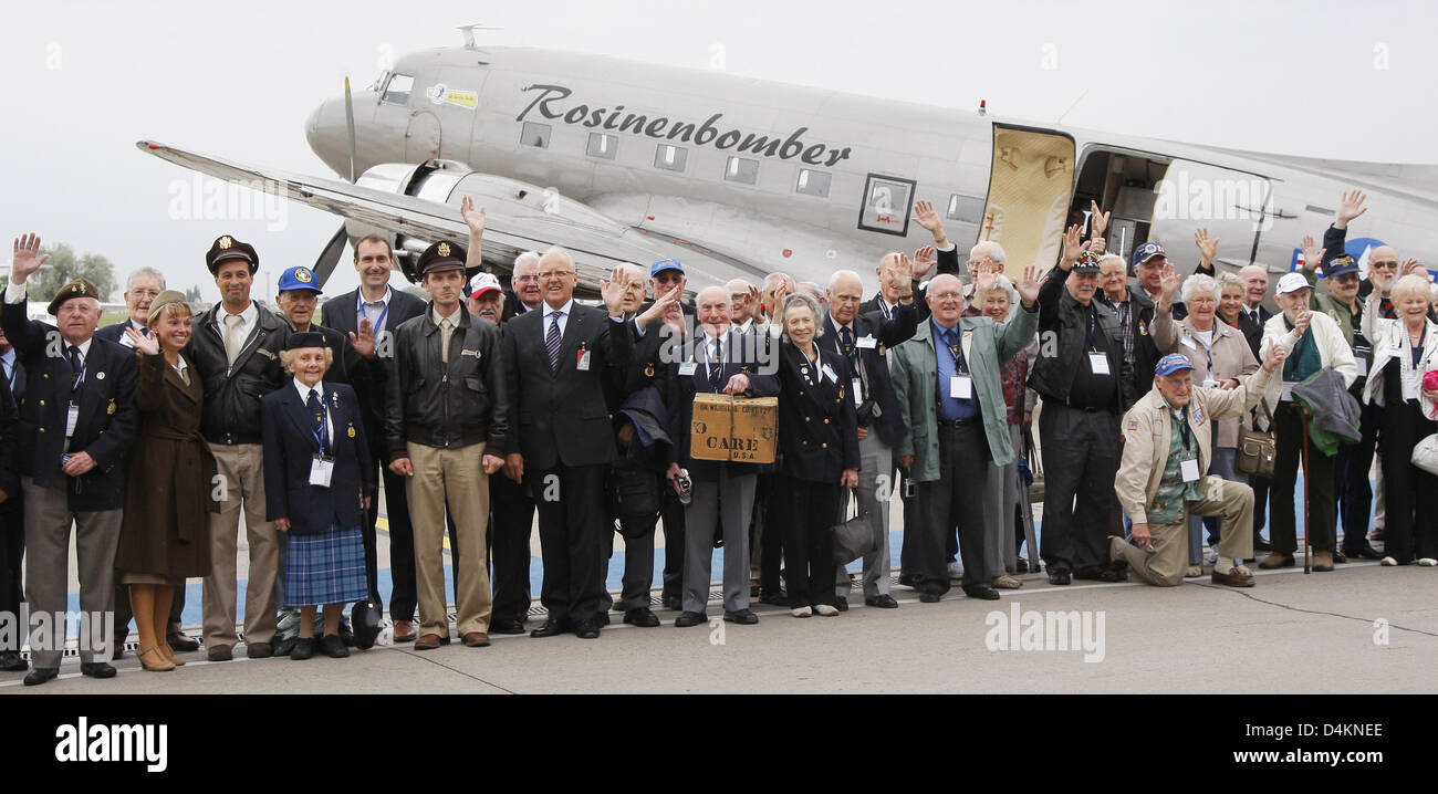 Berlin Air Lift veterans pose with a Care Paket in front of a classic transport plane type DC-3 at Schoenefeld airfield, - Stock Image