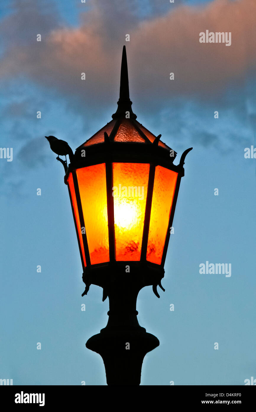 Lit old street lamp at sunset in Argentine. - Stock Image