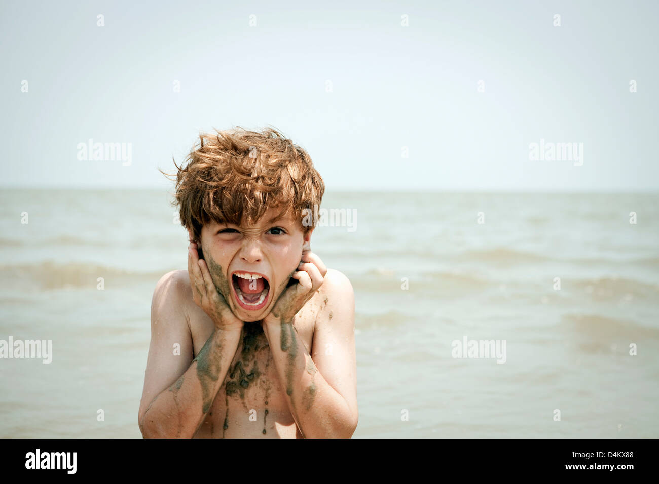 Boy playing with wet sand on beach - Stock Image