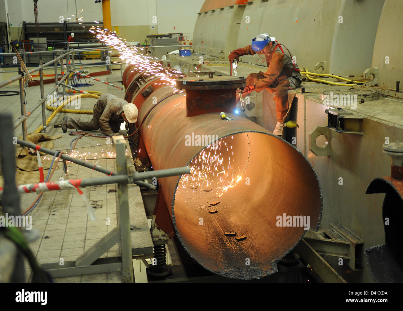 Workers dismantlwe copper pipes in the turbine house of the former atomic power plant in Obrigheim, Germany, 20 Stock Photo