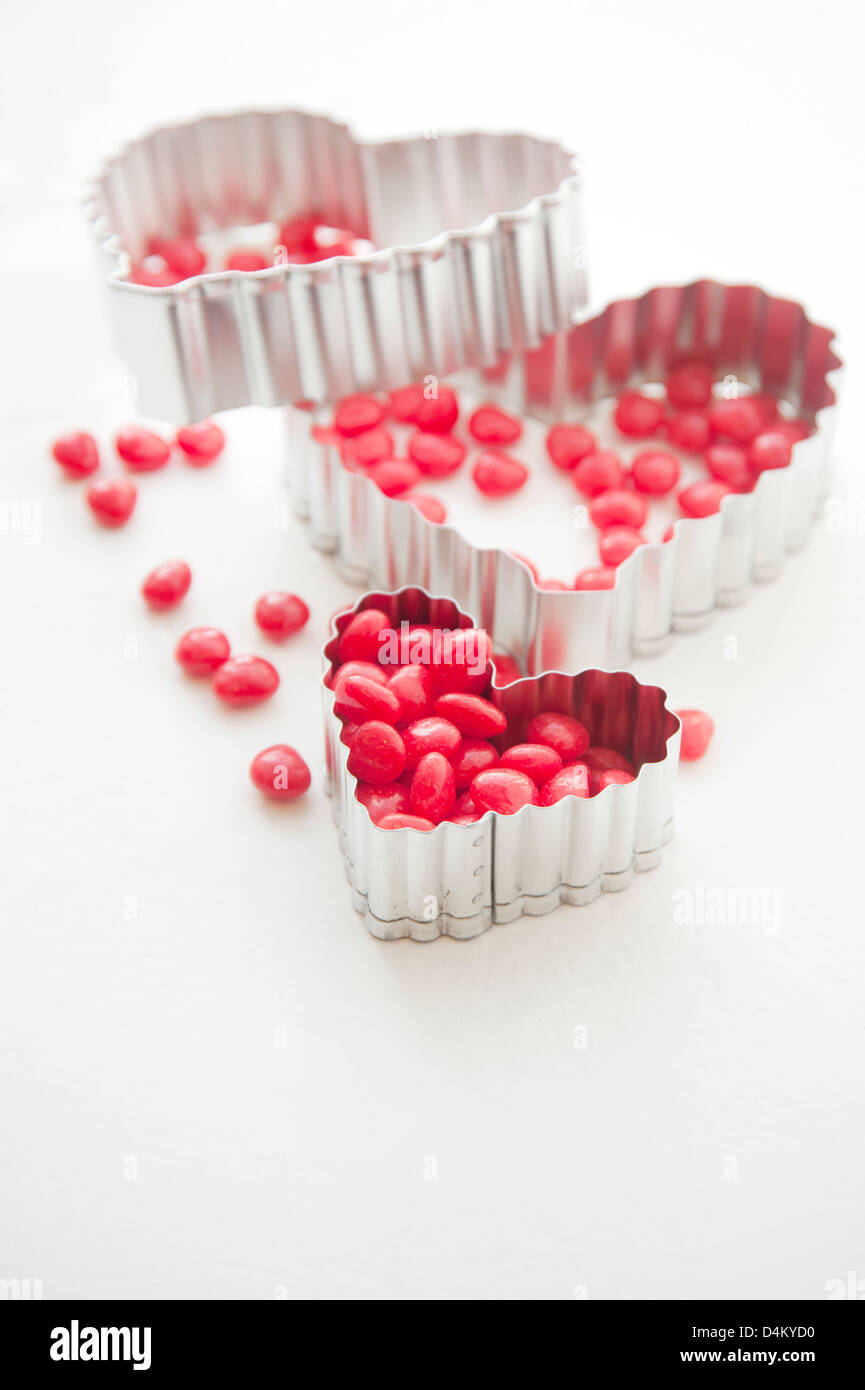 Heart shaped cookie cutters and heart shaped candy - Stock Image
