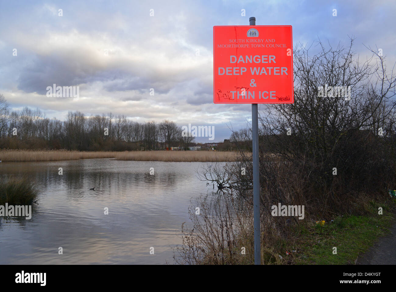 warning sign of deep water and thin ice by pond Yorkshire United Kingdom - Stock Image