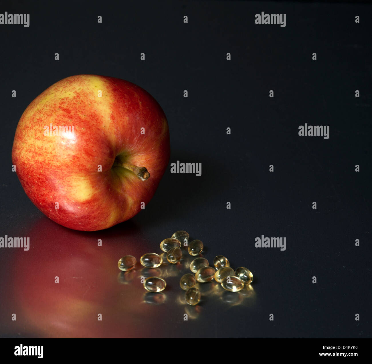 Red apple laying beside pile of vitamins - Stock Image