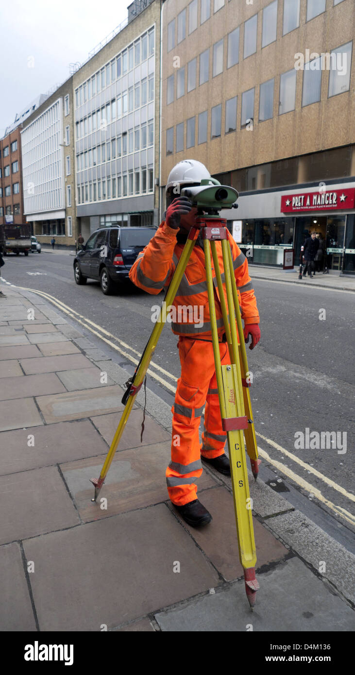 Surveyor working in a London street near Smithfield London England UK   KATHY DEWITT - Stock Image