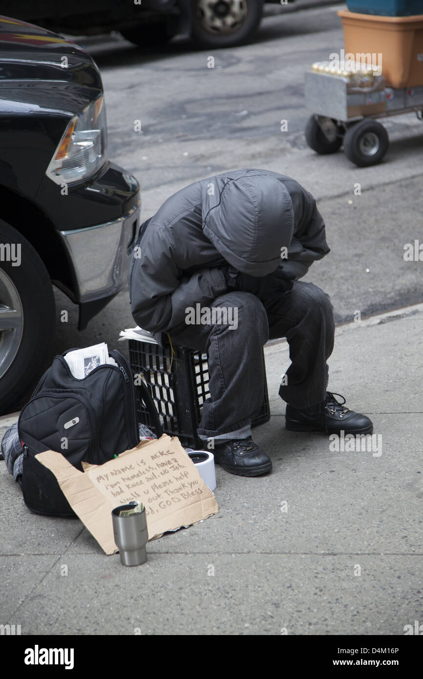 Homeless man begging on the street along 5th Avenue in New York City. - Stock Image