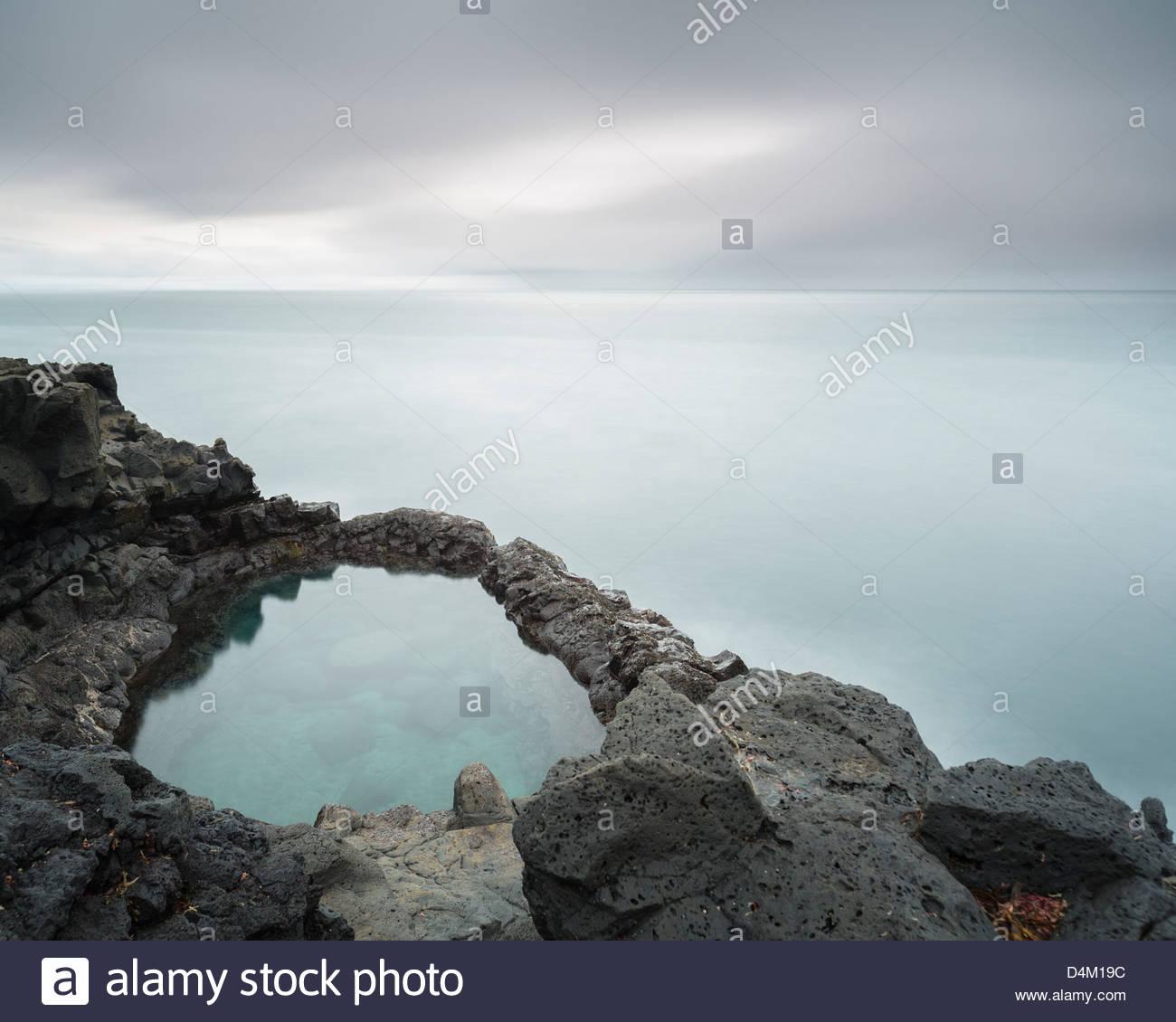Still rock pool in ocean - Stock Image