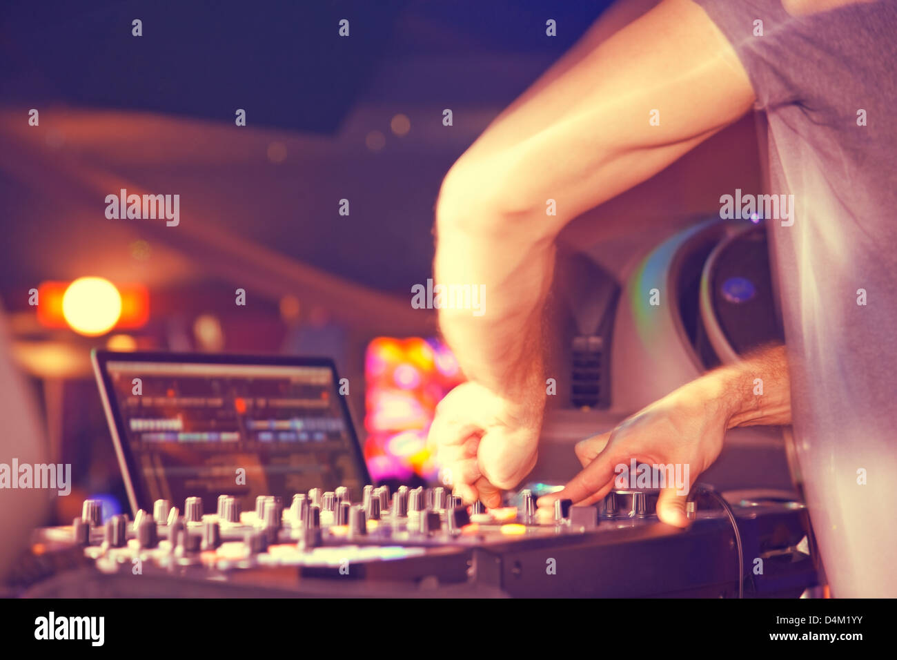 DJ behind the decks in night club Stock Photo