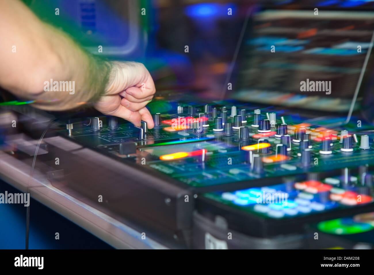 DJ behind the decks in night club - Stock Image