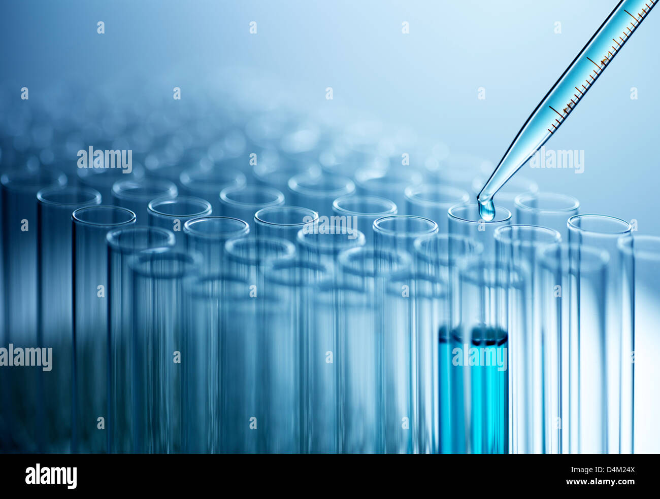Pipette dropping liquid into test tube - Stock Image