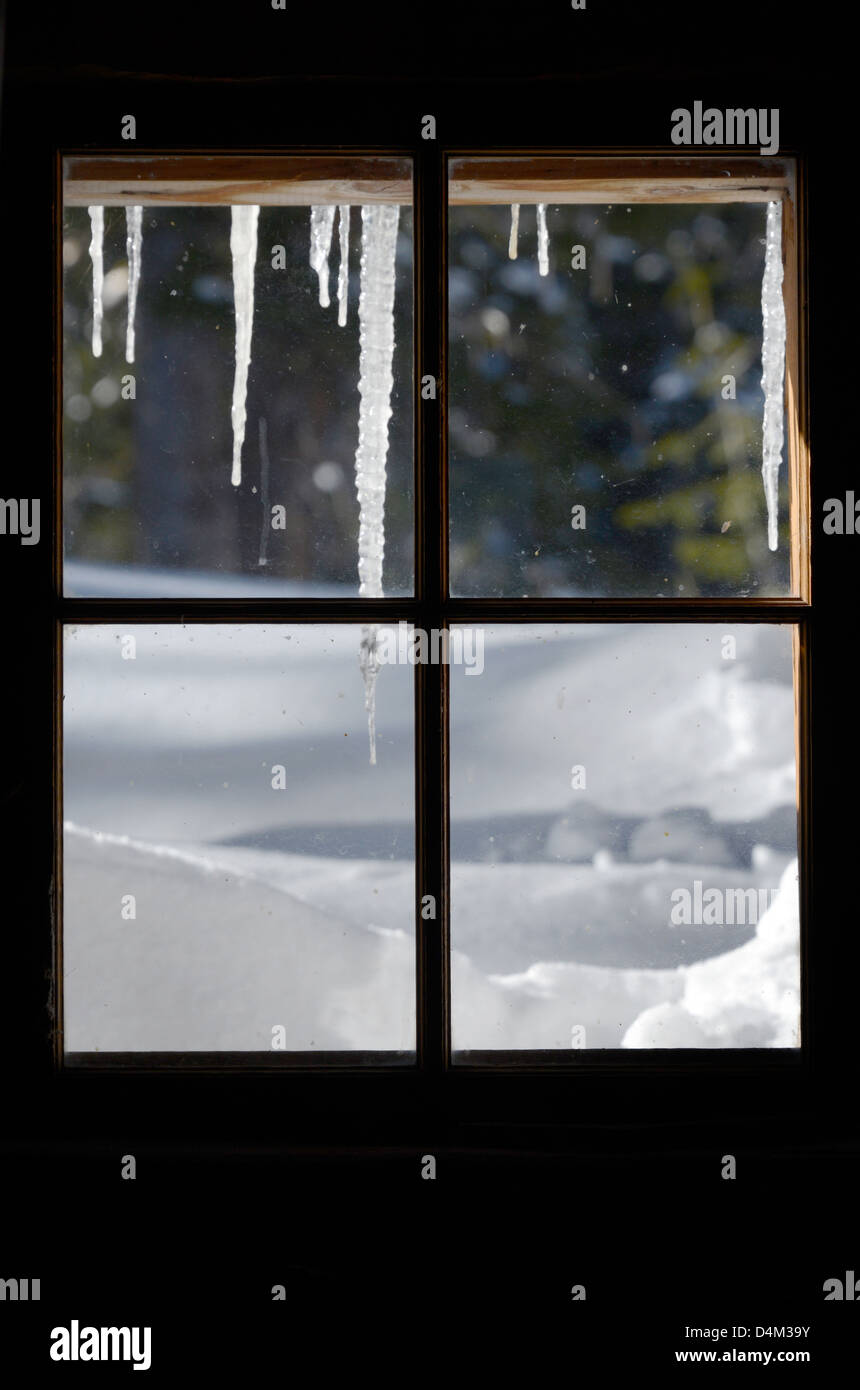 Icicles outside the window of an old cabin in Oregon's Wallowa Mountains. Stock Photo