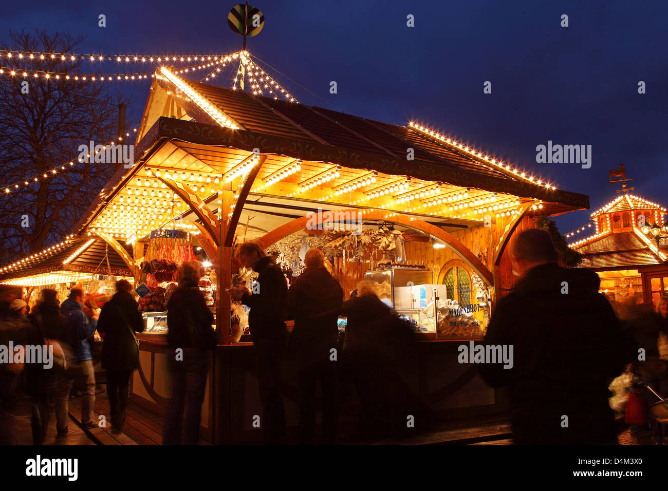 People meet around an illuminated stall at the Christmas Market (Weihnachtsmarkt) in Stuttgart, Germany. - Stock Image