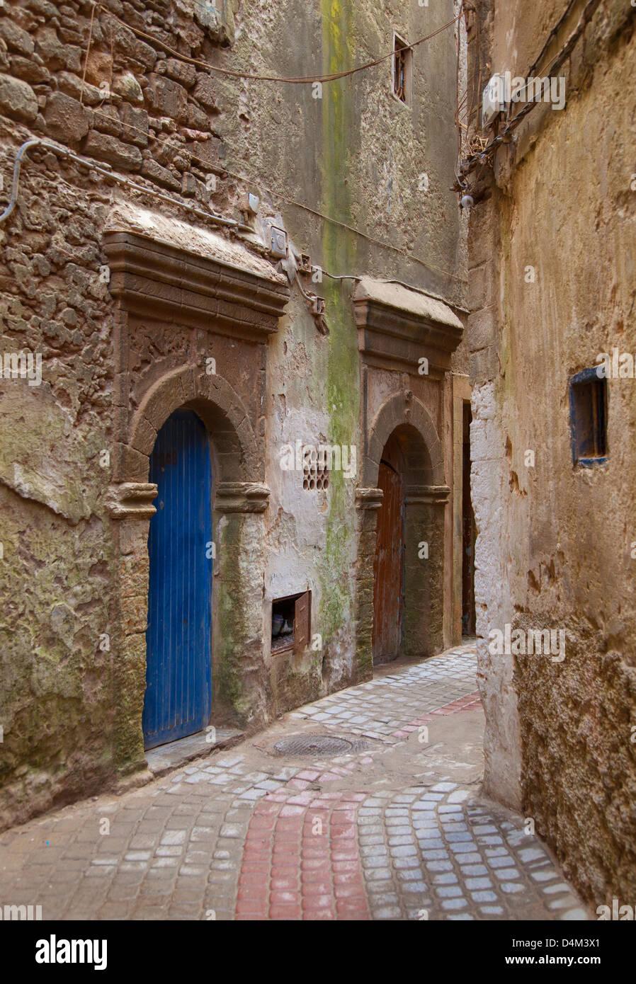 Arched doors in village alleyway - Stock Image