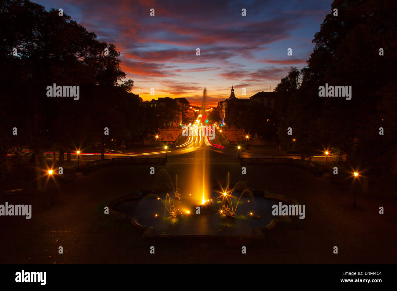 Ornate fountain with traffic at night - Stock Image