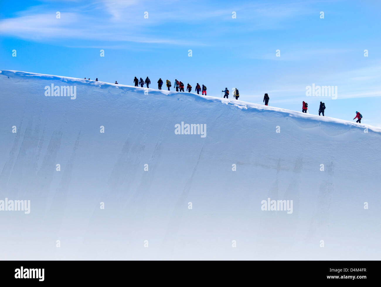 Expedition team members hiking on a glacier at Charlotte Bay in Antarctica - Stock Image