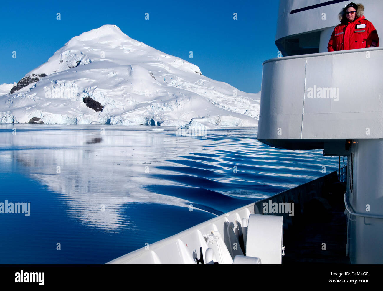 A tourist taking in the view at Paradise Bay in Antarctica - Stock Image