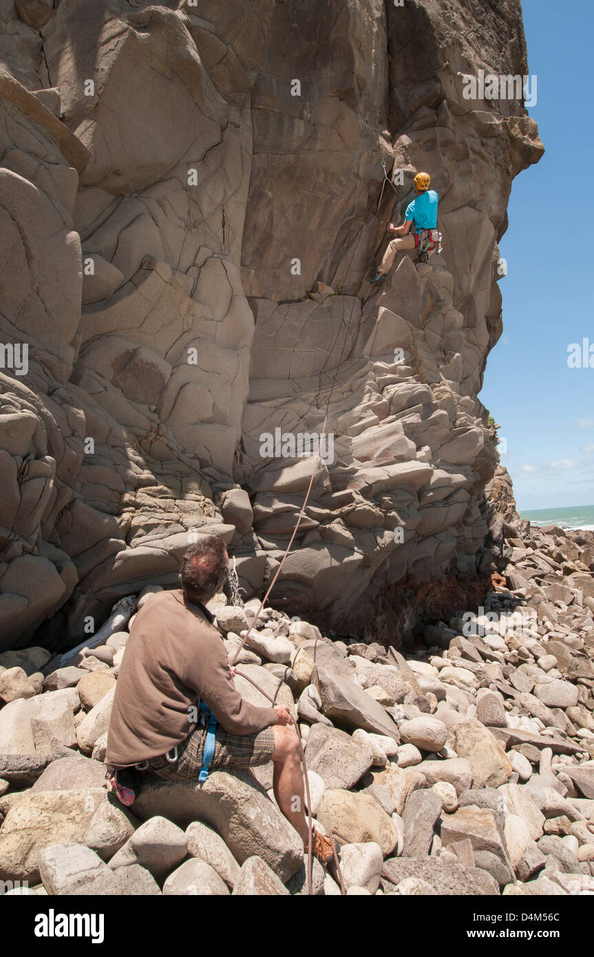 Rock climber scaling jagged cliff - Stock Image