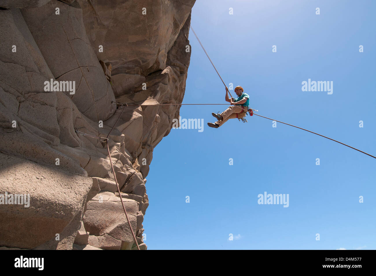Rock climber abseiling jagged cliff - Stock Image