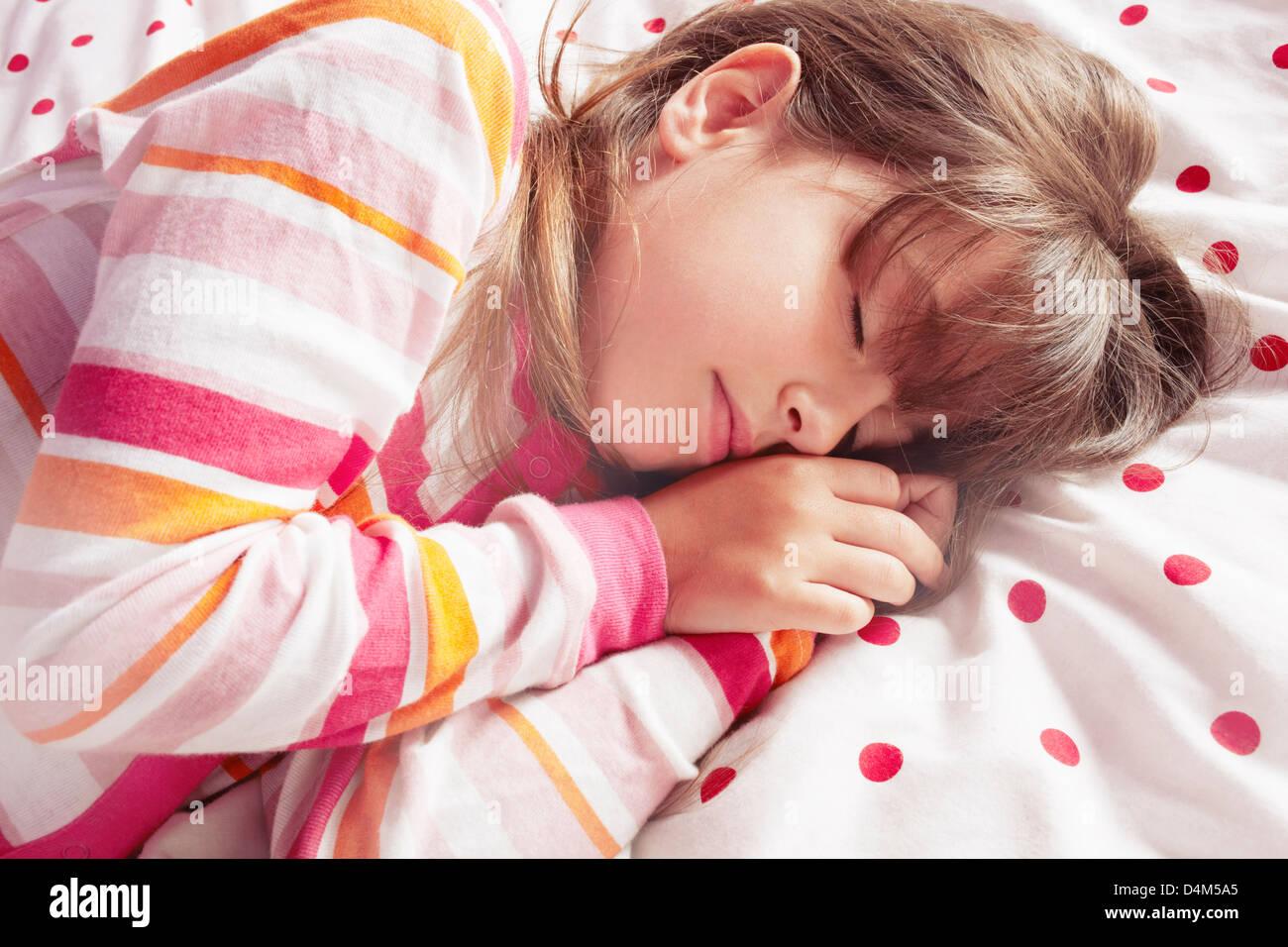 Girl sleeping on polka dot blanket - Stock Image
