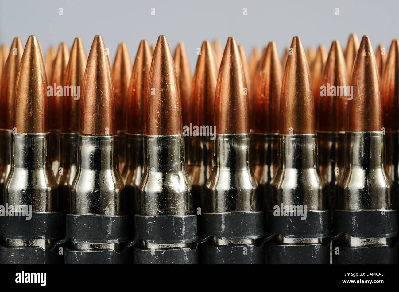 chain of bullets over white, close-up, horizontal - Stock Image