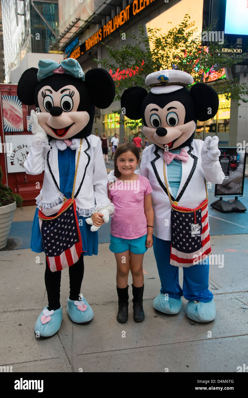 Mickey and Minnie Mouse cartoon character costumes posing with children in Times Square, New York - Stock Image
