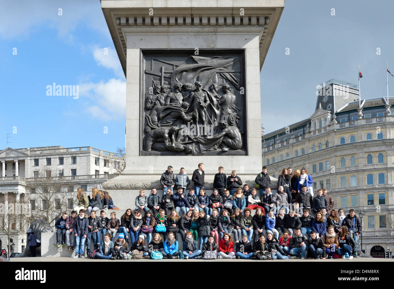Children on school trip posing for large group photo on Nelsons Column plinth - Stock Image