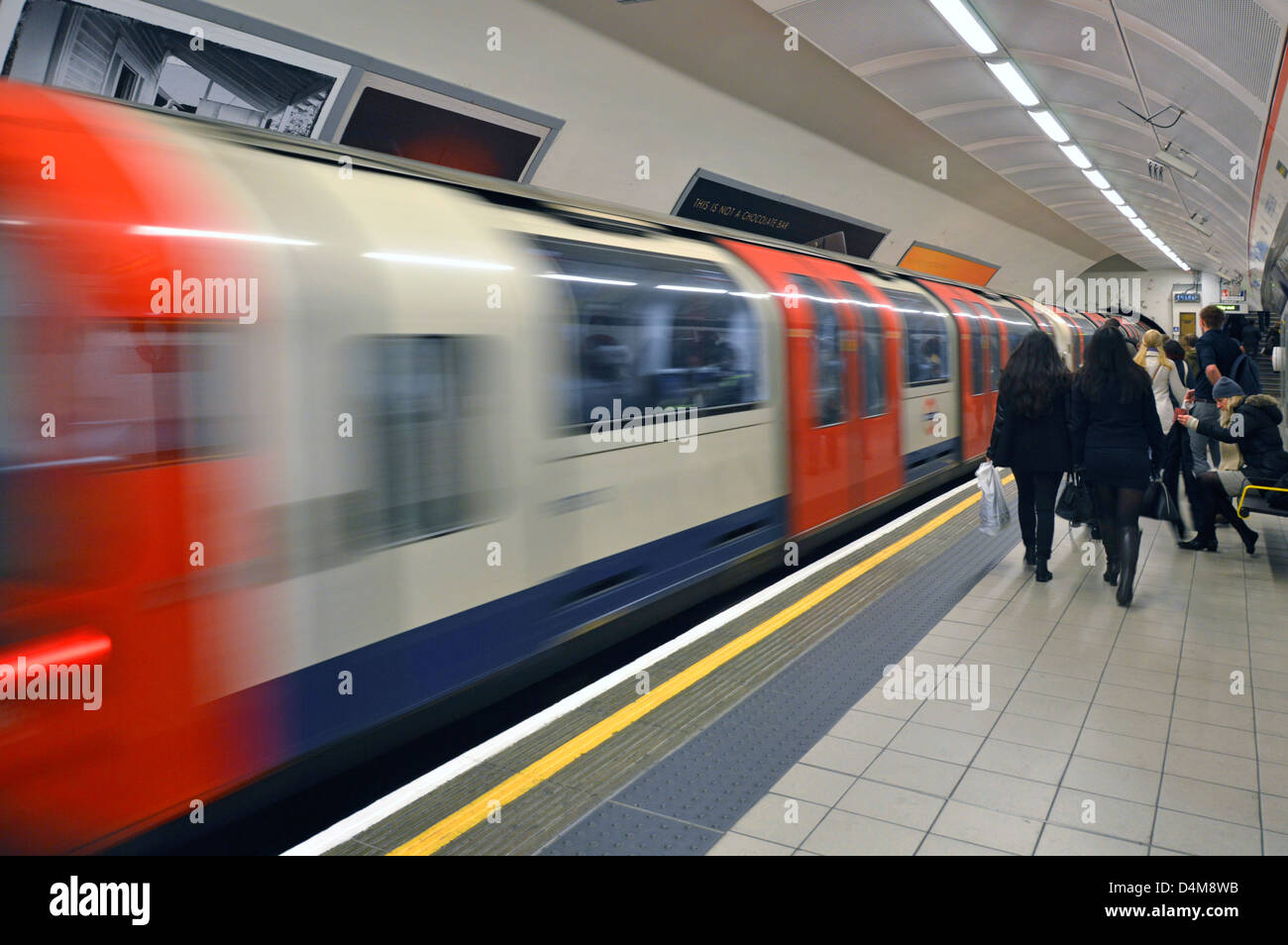 London Underground Central Line tube train departing train station people on platform with motion blur Shepherds - Stock Image