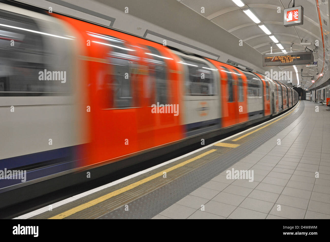 Empty platform on London Underground station with motion blur Central Line tube train departing  Shepherds Bush - Stock Image