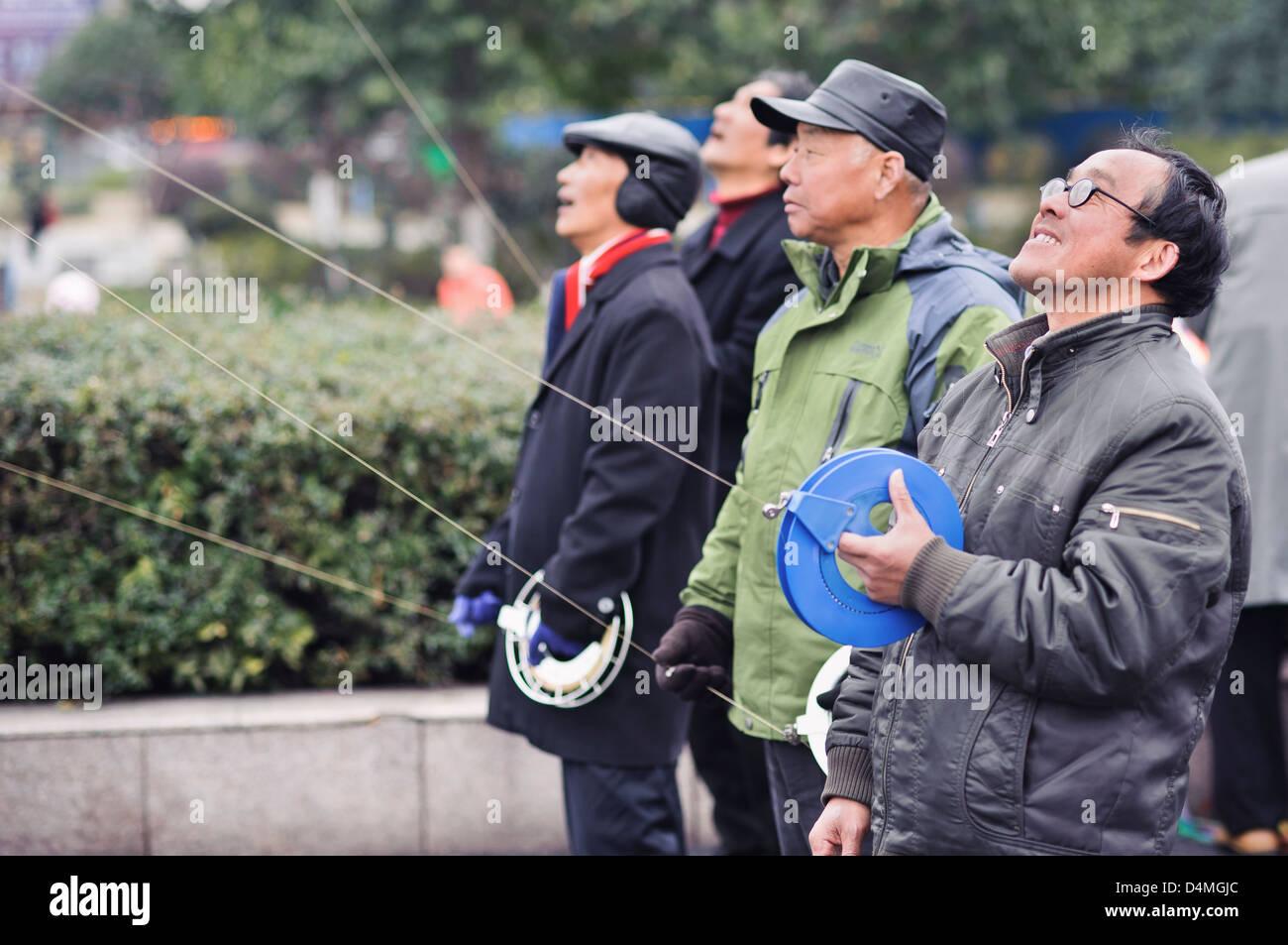 Local men flying kites in Wushan Square, Hangzhou, China - Stock Image