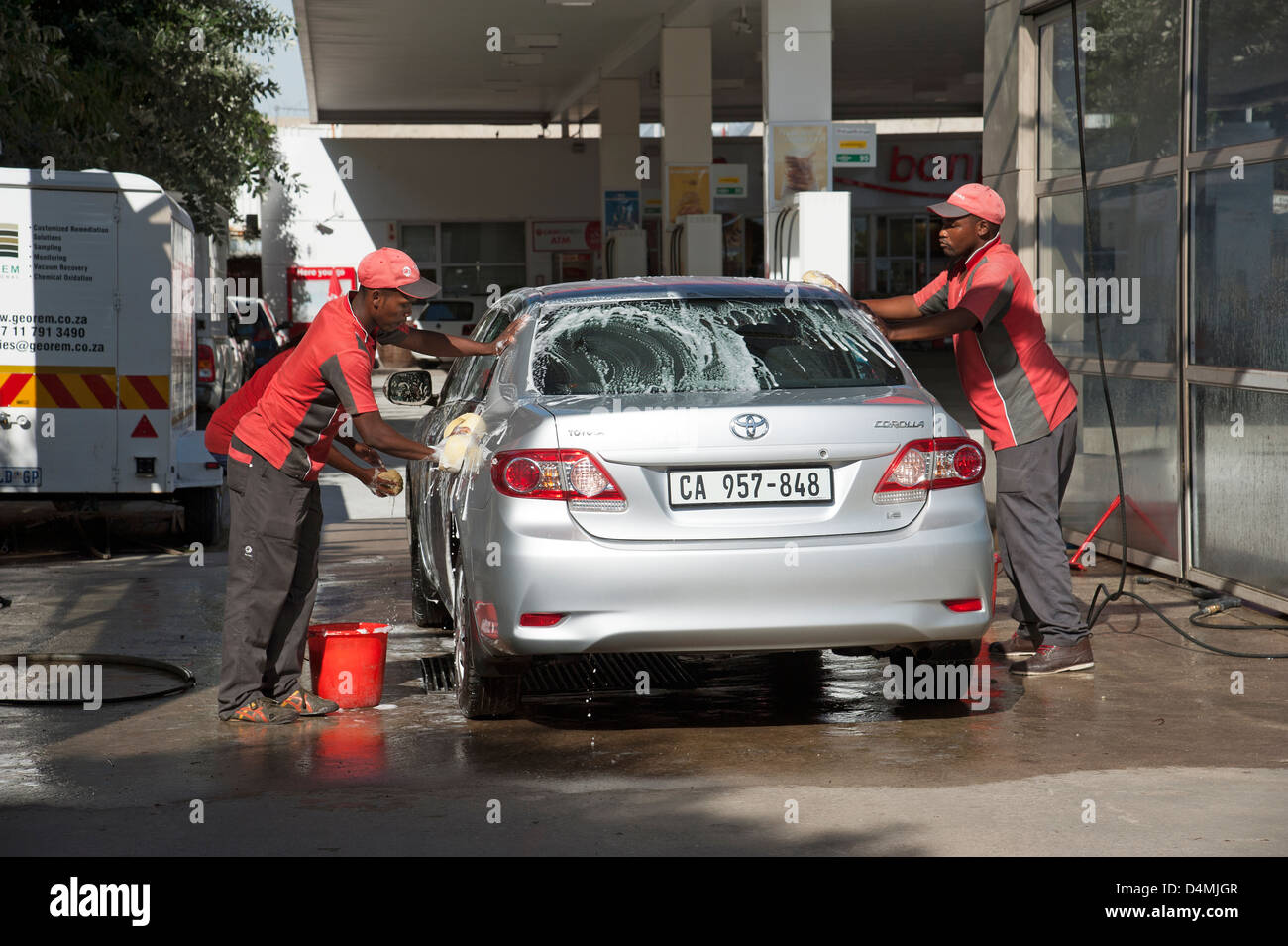 Hand car wash business washing and drying a vehicle - Stock Image