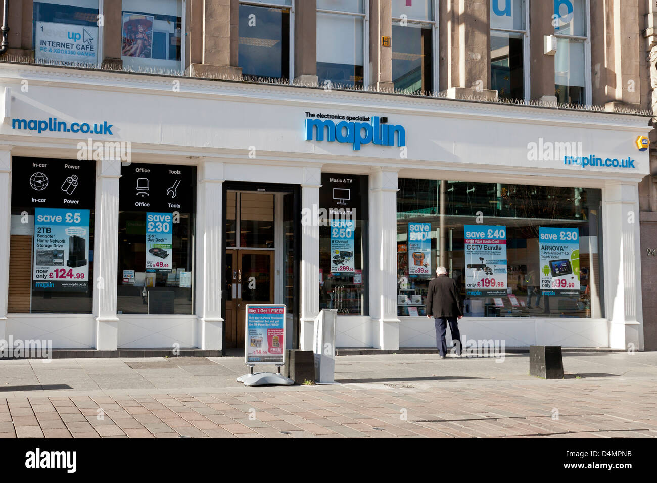 A man looking into the shop window of the Maplin (The Electronics Specialist) store in St Enoch Square in central - Stock Image