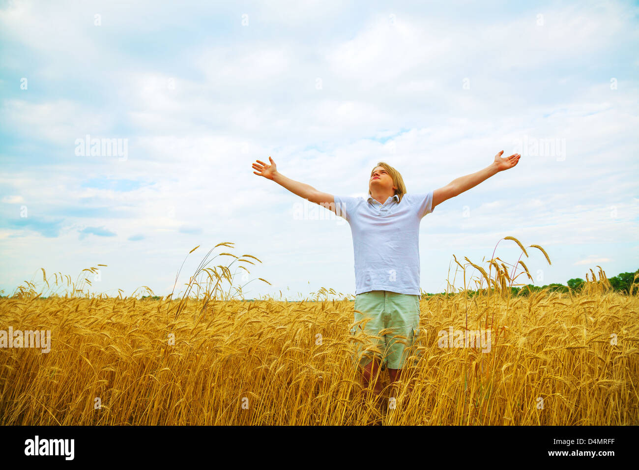 Young man staying with raised hands at sunset time - Stock Image
