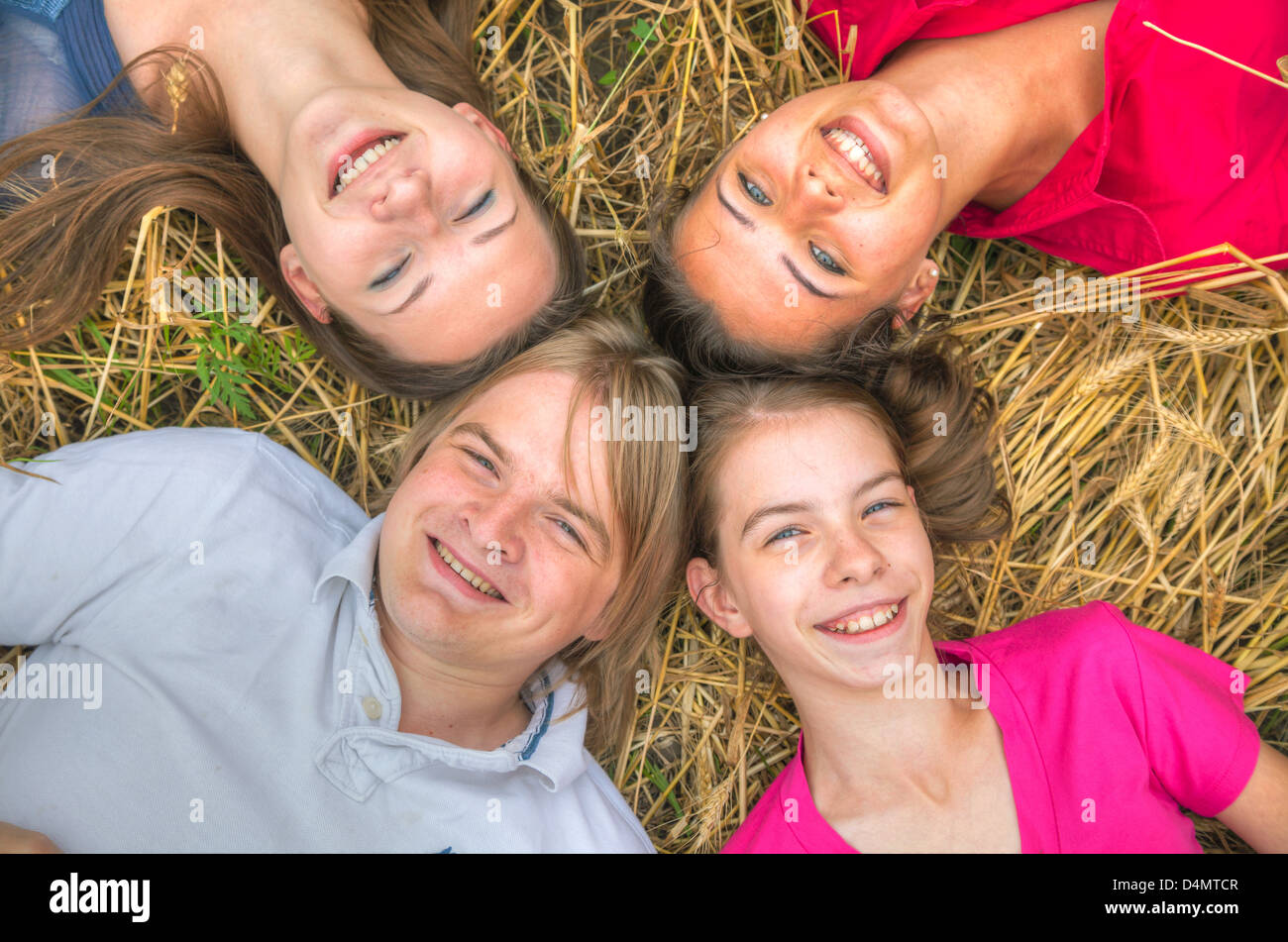 Four young happy people lying on the ground - Stock Image