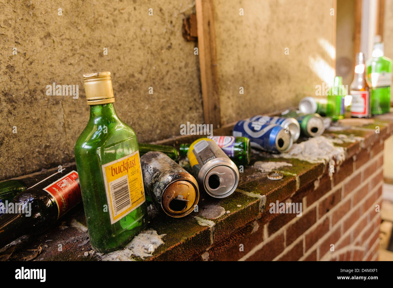 Lots of alcohol bottles and tins on the hearth of a very dirty house. - Stock Image