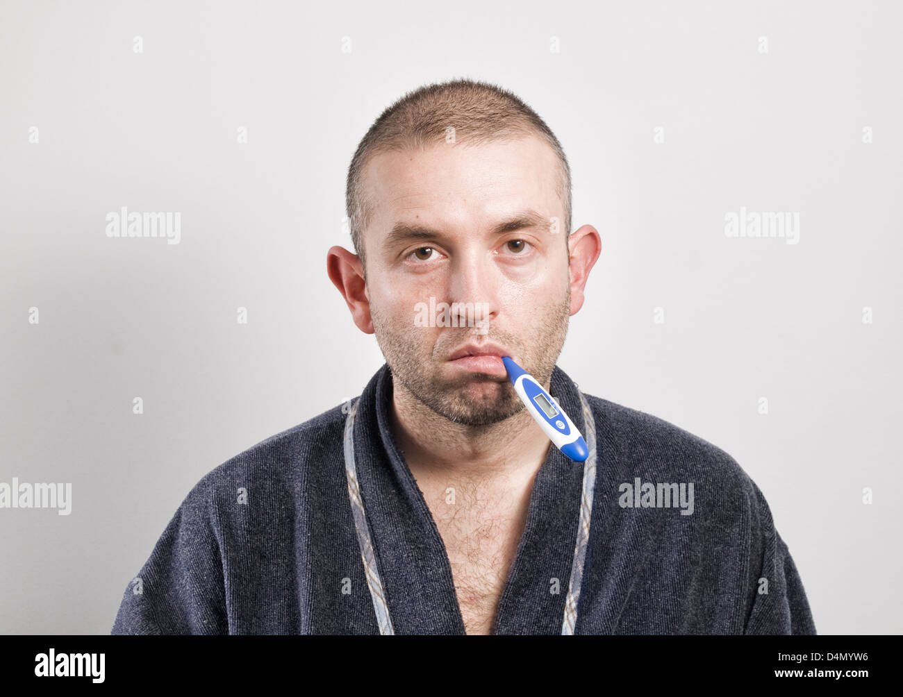 Sick man with thermometer on white background.rA normal man, no model. - Stock Image