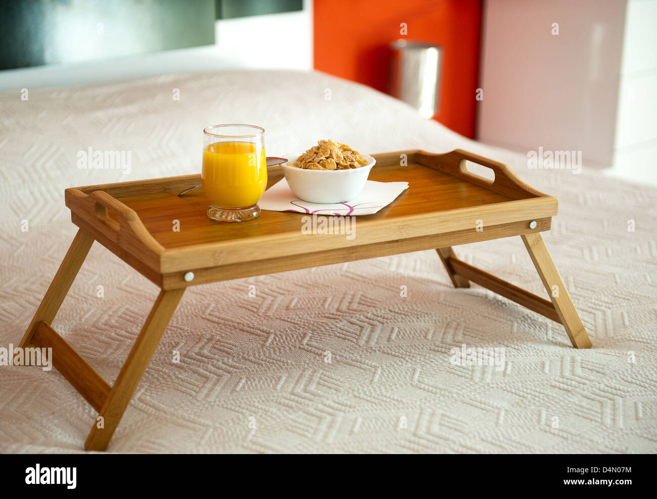 Breakfast with orange juice on a tray in bed - Stock Image