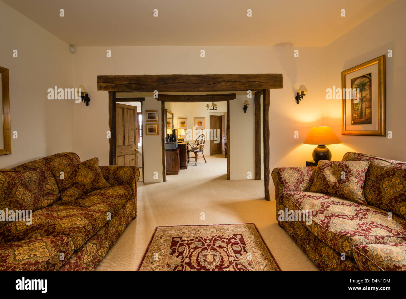 Cottage sitting room and office interior with oak beams and Delcor sofas - Stock Image