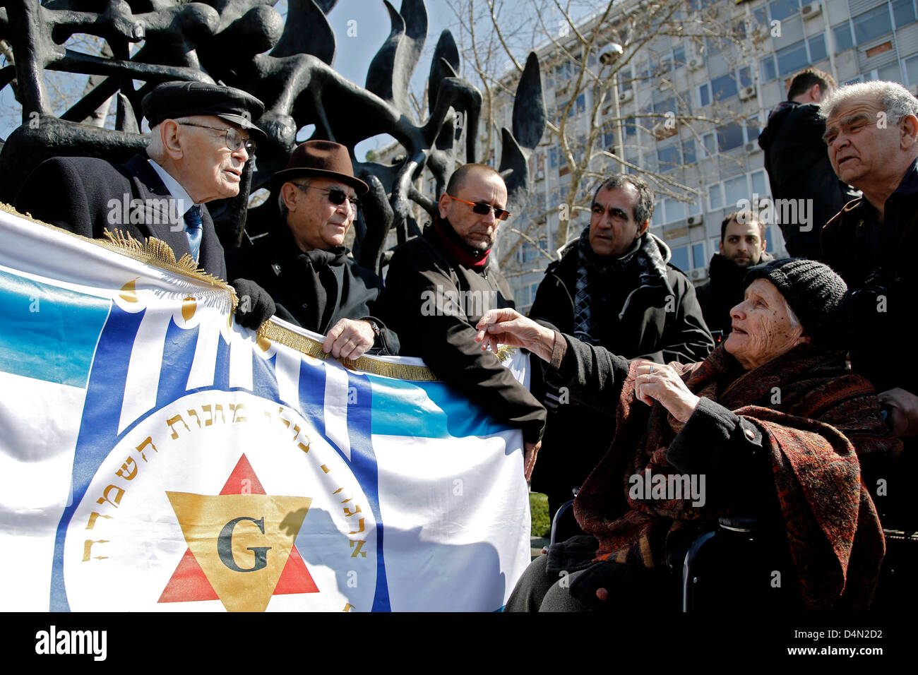 Holocaust survivors hold a flag of Greek-Jews Community and standing next to the Holocaust Memorial.  Commemorative - Stock Image
