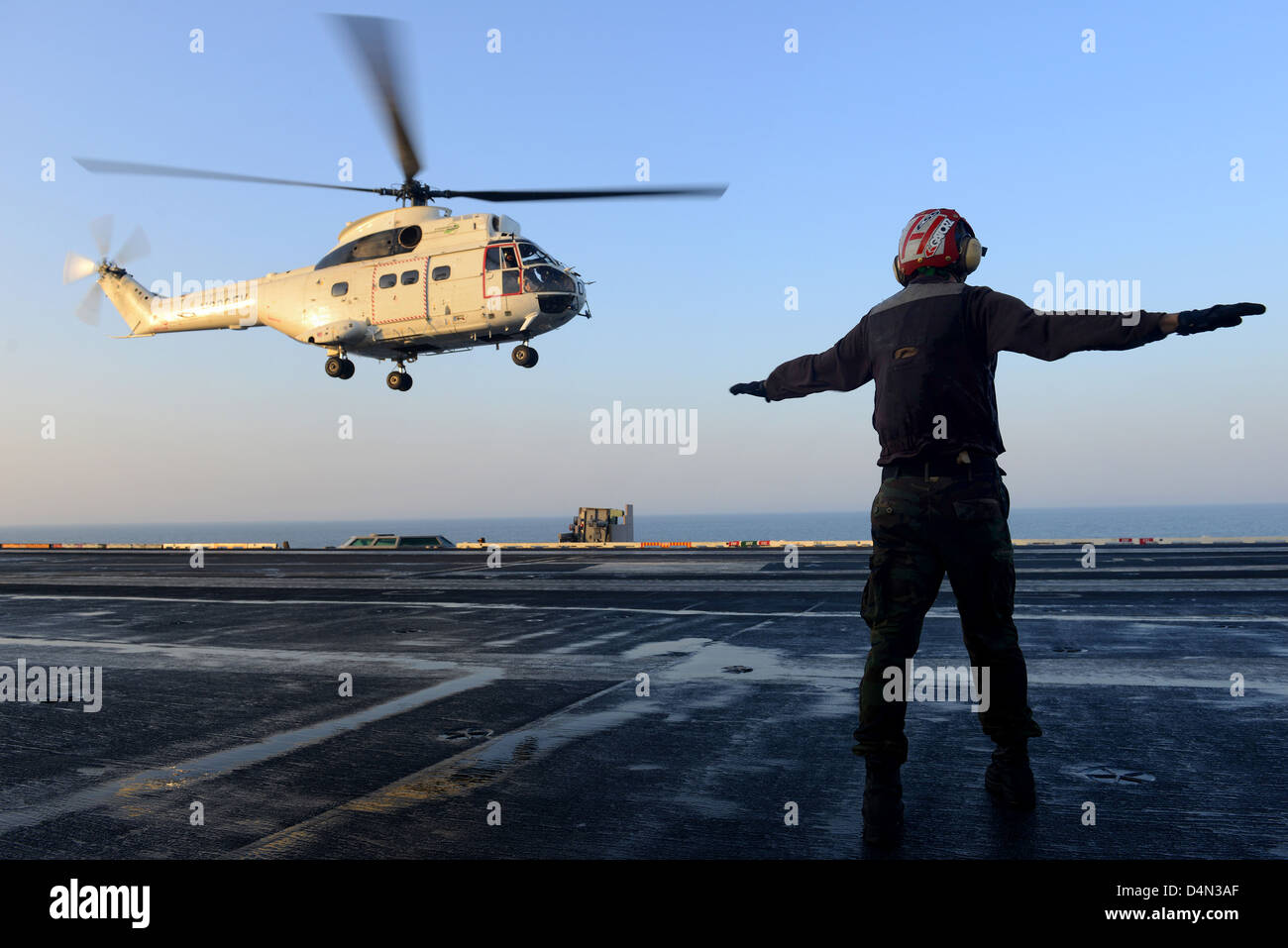 A US sailor signals a Military Sealift Command SA-330 Puma helicopter to take off from the aircraft carrier USS - Stock Image