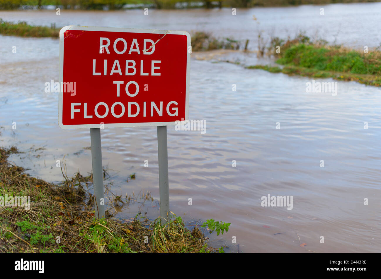 road liable to flooding sign, pictured surrounded by flood water, in Devon, UK Stock Photo