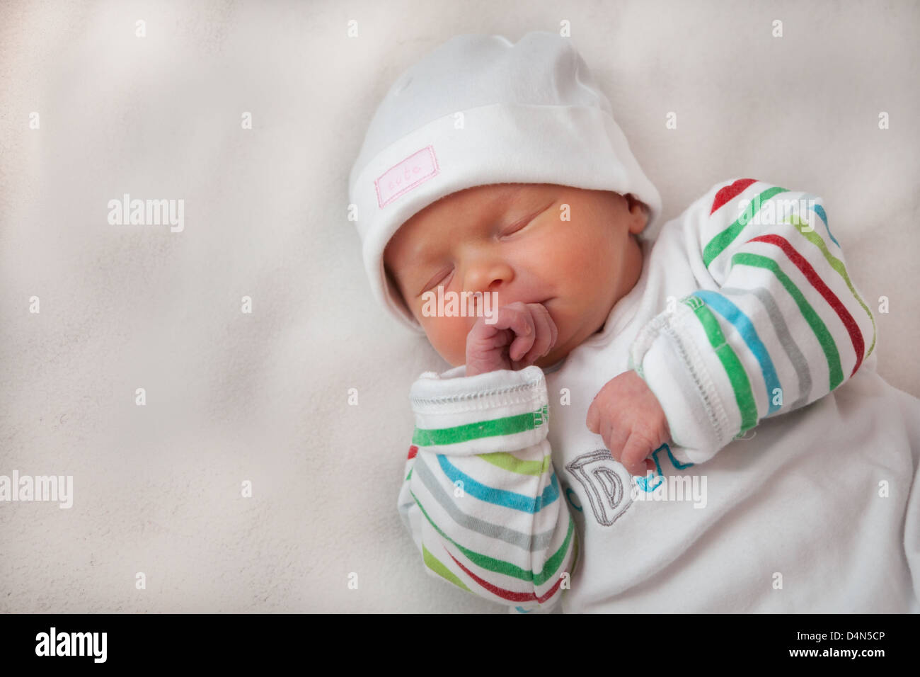 beautiful baby girl (8 days old) clutching her hands. taken in a
