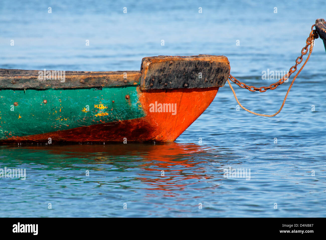 Anchored wooden fishing boat with reflection in water - Stock Image