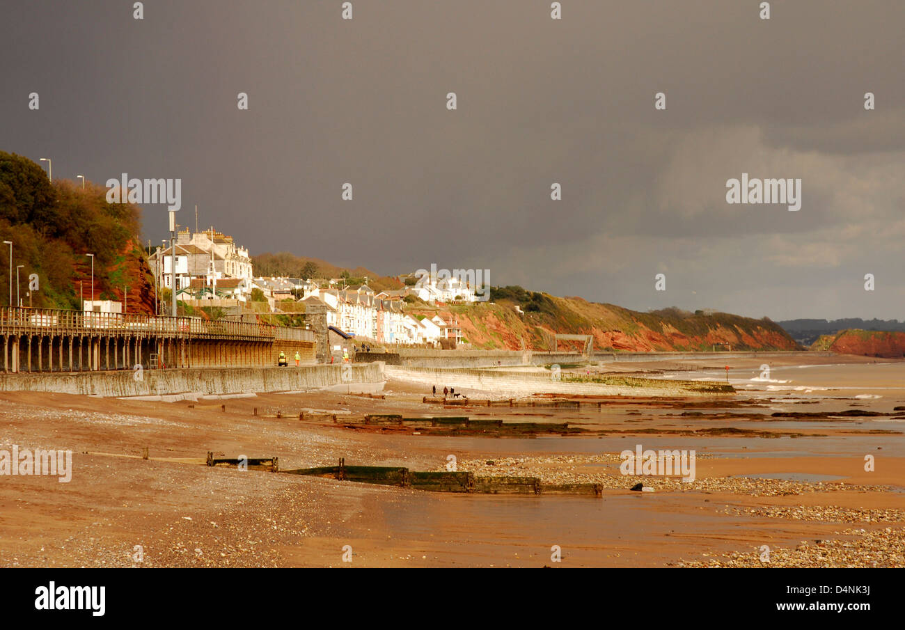 Devon - Dawlish beach and seafront buildings - dramatic storm clouds - winter sun picking out seafront - dark red Stock Photo