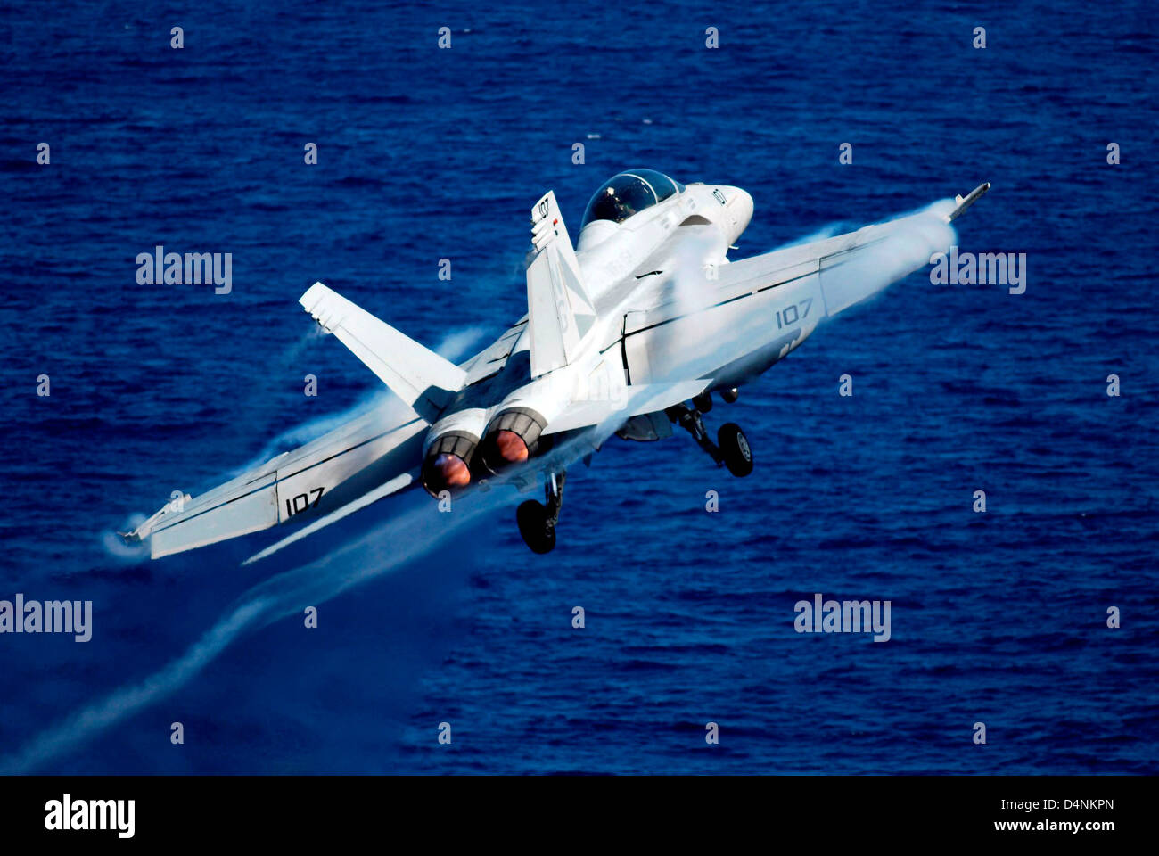 A US Navy F/A-18C Hornet fighter aircraft launches from the Nimitz-class aircraft carrier USS John C. Stennis February - Stock Image