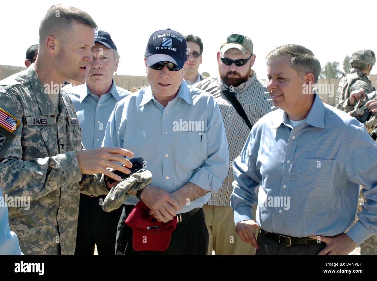 US Senator John McCain (center) listens to Col. Thomas James and Senator Joseph Lieberman (right) during a walk - Stock Image