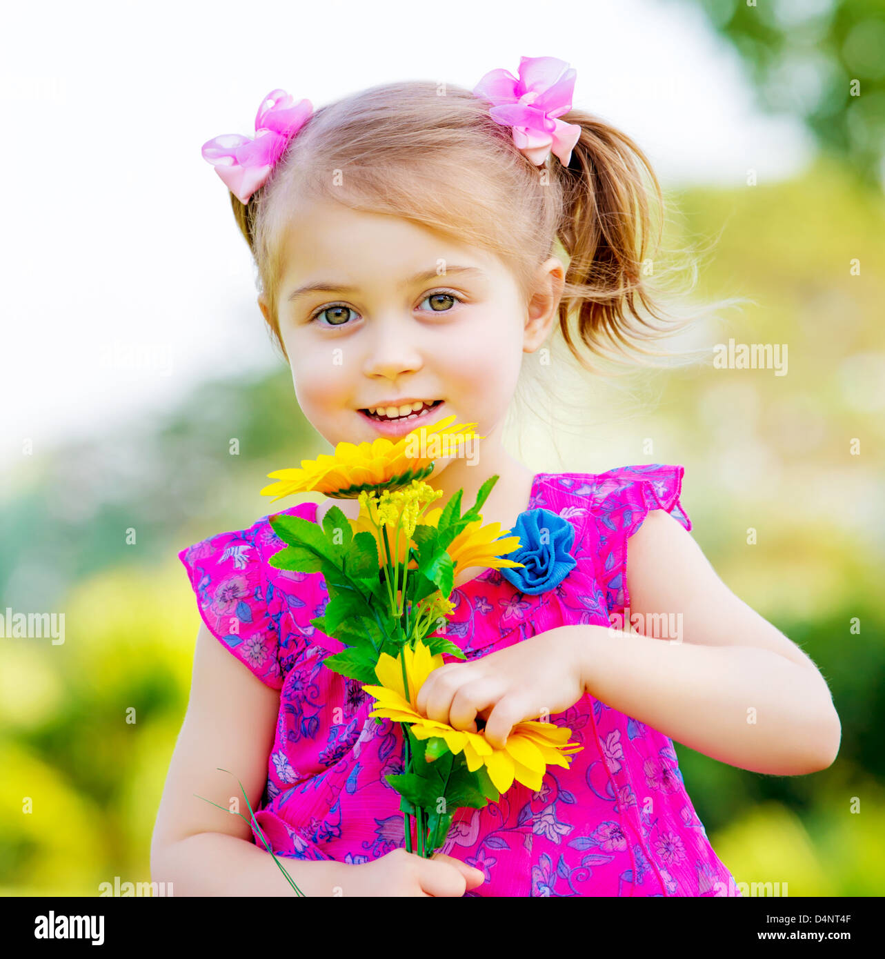 Happy baby girl playing outdoor cute child holding fresh sunflower flowers kid having fun in summer park